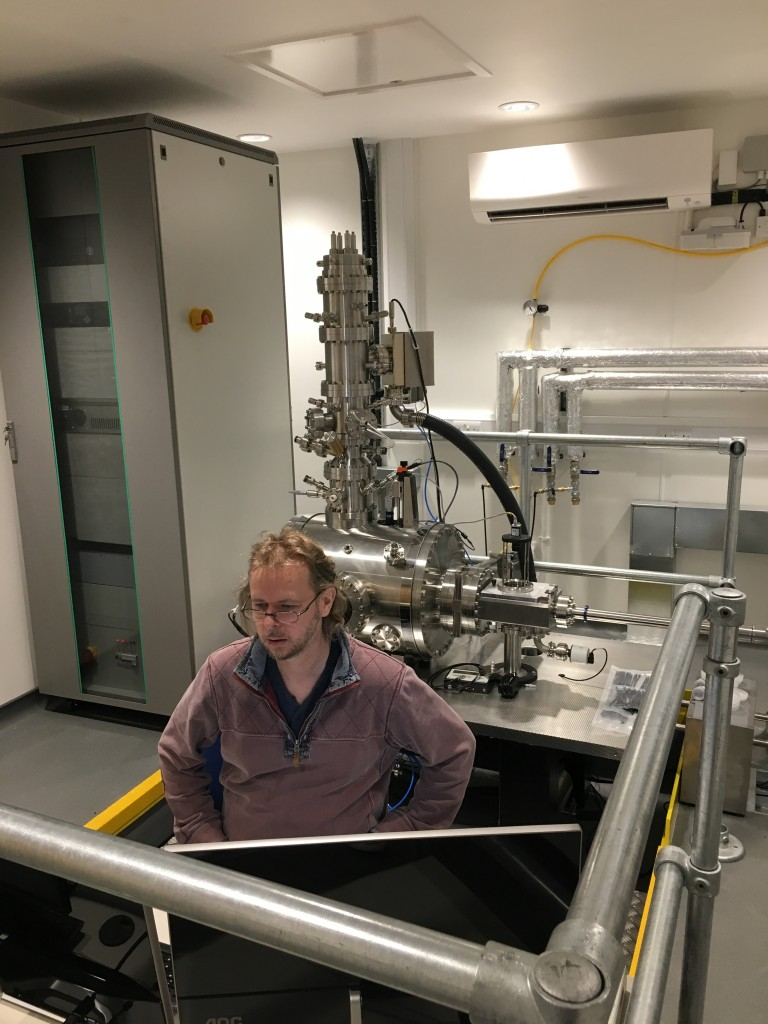 Dr David Cox, a focussed ion beam expert from the University of Surrey and the National Physical Laboratory performing commissioning tests at the console of the new SIMPLE tool in its new laboratory at Surrey.